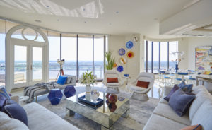 Contemporary living room with waterfront views and bold color.